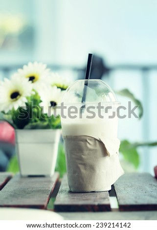 Vintage milk shake  with a flower in coffee shop. - stock photo