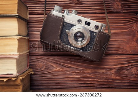 Vintage 35mm Film Camera and Stack of Books Over Wooden  Background - stock photo