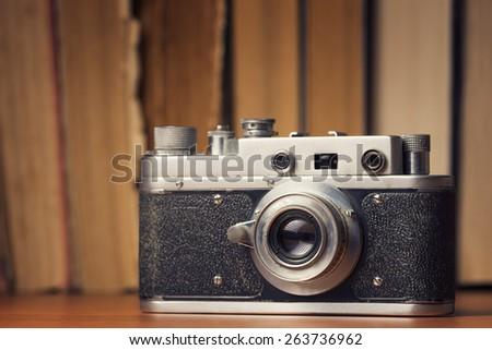 Vintage 35mm film camera over old books defocused background - stock photo