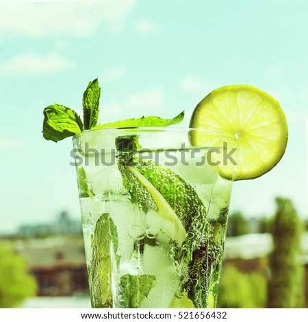 Vintage. Mojito in a glass on a background of a modern city and blue sky with clouds. Closeup. Alcoholic or non-alcoholic cocktail.