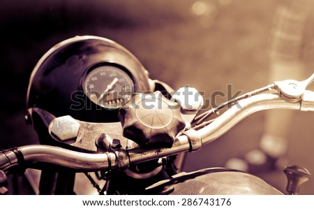 Vintage motorbike - oldtimer transport, toned old photo with sepia effect. Retro motorcycle with headlight and speedometer in monochromatic colors. - stock photo