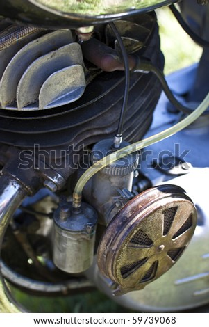 Vintage motorcycle engine with carburetor and rusty air filter - stock photo