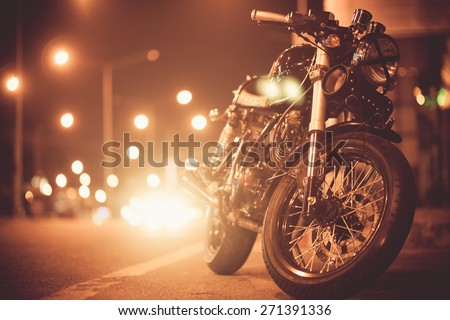 Vintage motorcycle on  road at night towards city - stock photo