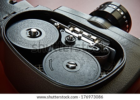 Vintage movie camera with film charged on reels - stock photo