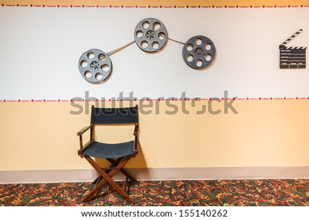Vintage Movie Making Icon Background including directors chair, 16mm film reels, and clapperboard. Copy space. - stock photo