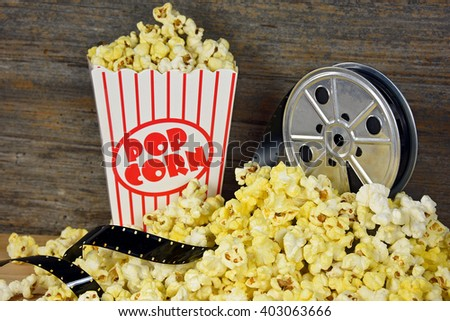 vintage movie reel and film with popcorn - stock photo