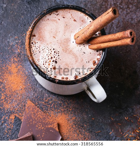 Vintage mug of hot chocolate with cinnamon sticks over dark background. Square image with selective focus - stock photo