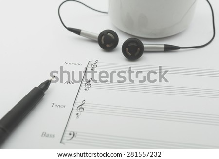 vintage music sheet earphone and cup - stock photo