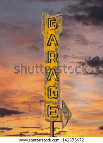 Vintage neon garage arrow sign with sunset sky. - stock photo