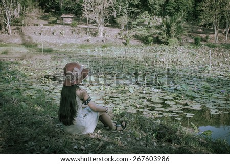 vintage of child girl sitting at the swamp - stock photo