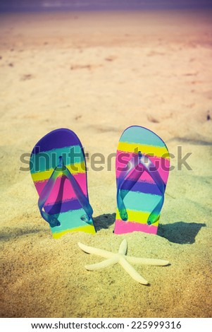 Vintage of colorful flip-flops on sand beach