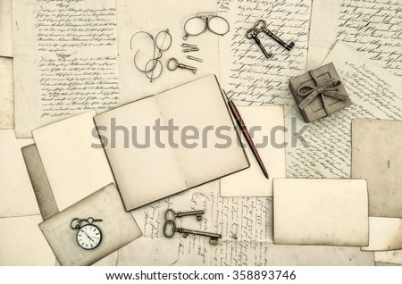 Vintage office accessories, open diary book and old handwritten letters. Nostalgic paper background - stock photo