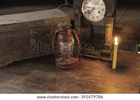 Vintage oil lamp ,old wooden box ,alarm clock and candlelight on old wooden touch-up in still life concept,in black and white tone - stock photo