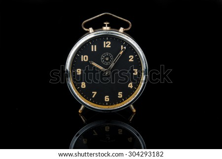 Vintage old analog alarm clock with reflection over black background. - stock photo
