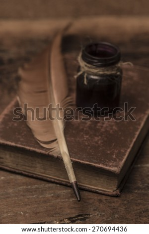 Vintage old books, scrolls, feather pen and inkwell on wooden table