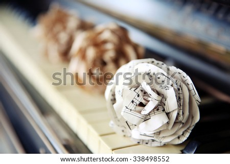 Vintage old classic piano with paper rose and musical notes on it, close up - stock photo