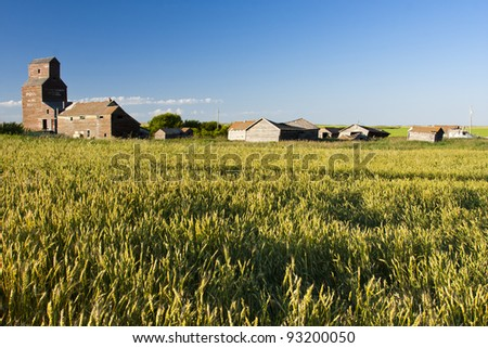 Vintage old-fashioned buildings abandoned in an old ghost town beyond a rural field - stock photo
