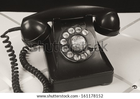 Vintage Old Fashioned Phone - Antique Black Phone On a Decorative Background - stock photo