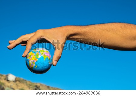 Vintage Old Globe Earth and Human Hand over a Blue Sky - stock photo