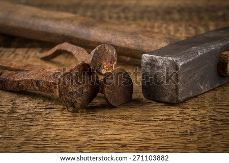 Vintage old hammer with rusty nails on wood table background - stock photo