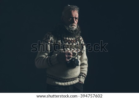Vintage old mountaineer with knitted sweater, fur collar and SLR camera. - stock photo