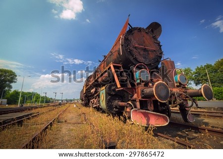 vintage old rusty steam train under sunny blue sky - stock photo