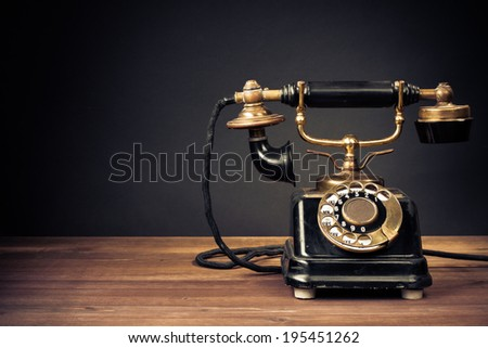 Vintage old telephone front black background - stock photo