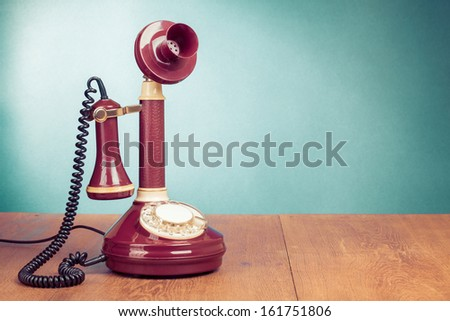 Vintage old telephone on wood table near aquamarine wall background - stock photo