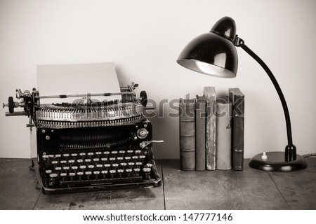 Vintage old typewriter, old books and retro lamp on table - stock photo