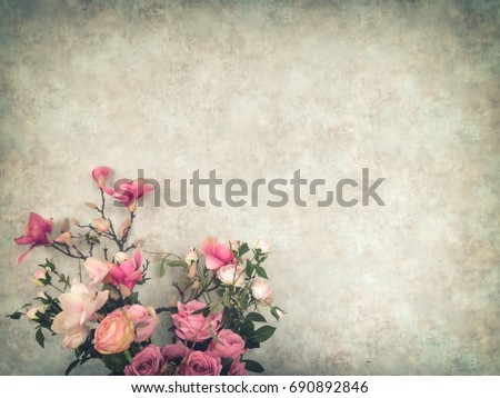 Vintage old wall background with grain texture decorated with pink flowers and roses in antique vase with copy space for text decoration and insertion
