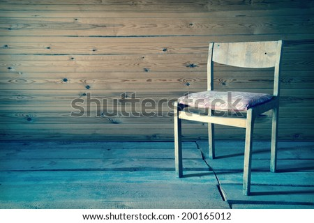 Vintage old wooden chair in grungy interior. Loneliness, estrangement, alienation concept. Toned image - stock photo