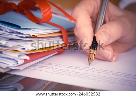 Vintage or retro style Hand with pen writing a letter by mail tied with ribbon closeup  - stock photo