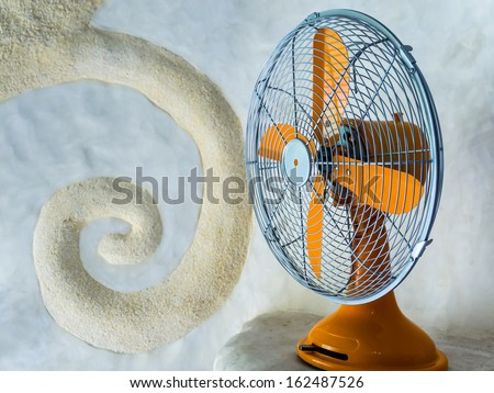 Vintage orange electric fan on Spiral bas-relief stucco wall  background - stock photo