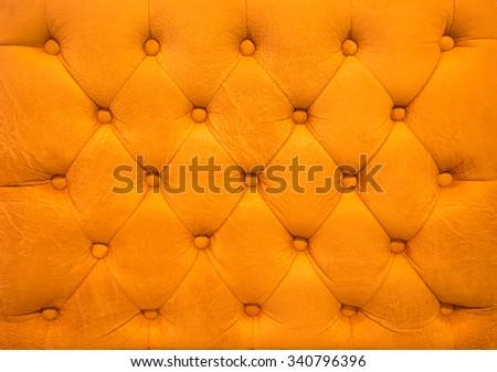 Vintage orange leather upholstery buttoned sofa (background) - stock photo