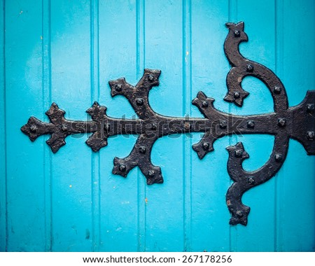 Vintage Ornate HInge On A Bright Blue Painted Church Door - stock photo