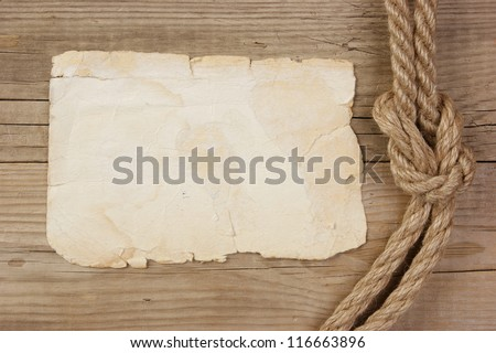 Vintage paper and rope on old wooden boards - stock photo