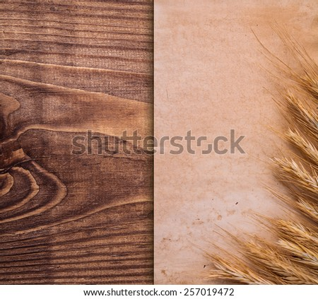 vintage paper with ears of wheat on old wooden board  - stock photo