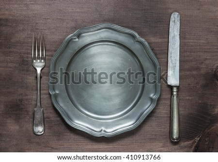 Vintage pewter plate, fork and knife on old dark wooden board - stock photo