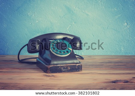 Vintage phone on a wooden table - stock photo