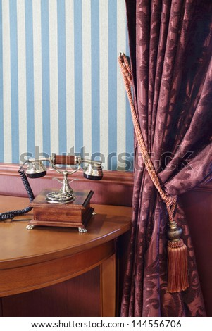 Vintage phone on table near wall with striped wallpaper and curtain with cord brush. - stock photo