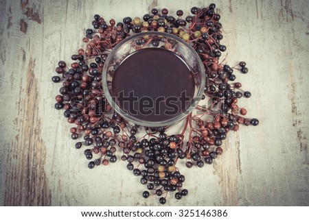Vintage photo, Bunch of fresh elderberry and glass of elderberry juice on old rustic wooden background, healthy nutrition, alternative medicine and therapy - stock photo