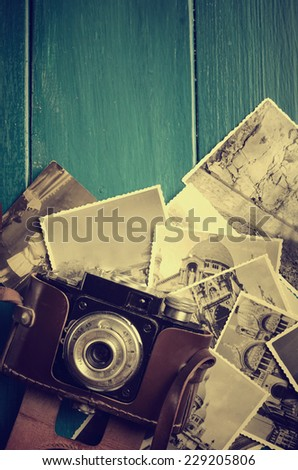 Vintage photo camera and old photos. - stock photo