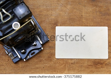 Vintage photo camera with blank photo frame on a wooden table - stock photo