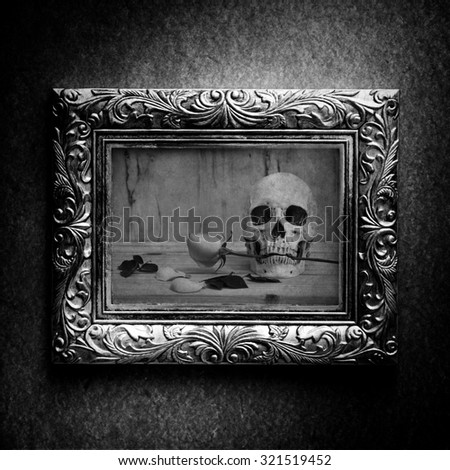 Vintage photo frame, photo of skull with rose over grunge background, halloween concept, black and white  - stock photo