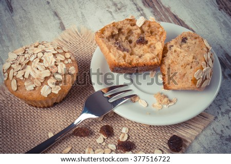 Vintage photo, Fresh muffins with oatmeal baked with wholemeal flour on white plate and fork, concept of delicious, healthy dessert or snack