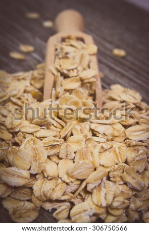 Vintage photo, Heap of organic oatmeal, oat flakes with wooden spoon on wooden background, concept for healthy eating and nutrition