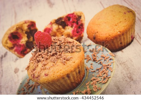 Vintage photo, Homemade fresh baked muffins with raspberries and grated chocolate on plate, old rustic wooden background, delicious dessert