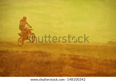 vintage photo of a biker making a stunt and jumps on motorbike - stock photo