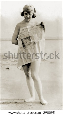 Vintage photo of a Girl On Beach Covering Self With Newspaper - stock photo