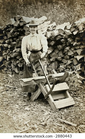 Vintage Photo of a woman sawing firewood - stock photo